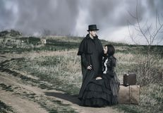 Outdoors portrait of a victorian lady in black sitting on the road with her luggage and gentleman standing nearby stock image