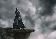 Outdoors portrait of a victorian lady in black standing on the cliff royalty free stock photos