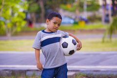 Outdoors portrait of 5 or 6 years old young Asian Indonesian kid posing happy with soccer ball playing football in child sport stock photos