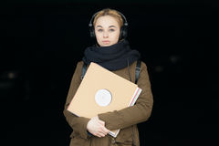 Outdoors portrait of young beautiful blonde hipster woman in big dj headphones with a vinyl records Stock Photo