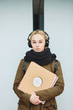 Outdoors portrait of young beautiful blonde hipster woman in big dj headphones with a vinyl records Stock Photos