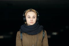 Outdoors portrait of young beautiful blonde hipster woman enjoying music in big dj headphones Royalty Free Stock Images