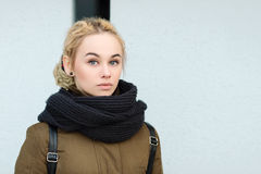 Outdoors portrait of young beautiful blonde hipster woman in olive parka with a dreadlocks bun hairstyle Royalty Free Stock Photo