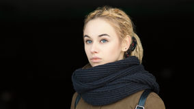 Outdoors portrait of young beautiful blonde hipster woman in olive parka with a dreadlocks bun hairstyle Stock Image