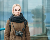Outdoors portrait of young beautiful blonde hipster woman photographer with a film camera Royalty Free Stock Images