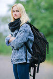 Outdoors portrait of a young beautiful blonde woman in jeans with a big old backpack Stock Images