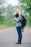 Outdoors portrait of a young beautiful blonde woman in jeans with a big old backpack Royalty Free Stock Image