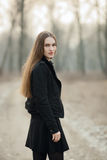 Outdoors portrait of young beautiful fashionable woman strolling at the evening in the forest park Royalty Free Stock Photos