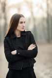 Outdoors portrait of young beautiful fashionable woman strolling at the evening in the forest park Stock Photos