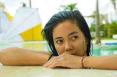 Outdoors portrait of young beautiful and sweet Asian Indonesian teenager girl swimming at tropical resort pool smiling happy and stock photos
