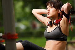 Outdoors portrait of young brunette girl doing exercising abdominals Stock Photography