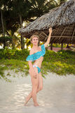Outdoors portrait of young woman standing near parasol on tropical beach. Stock Image