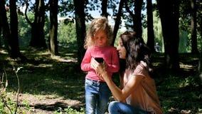 Outdoors portret rodzina Patrzeje Błękitnego Smartphone Wpólnie Młodzi brunetki matki przedstawienia Dlaczego Używać telefon komó zbiory wideo