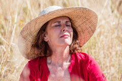 Outdoors relaxation - happy beautiful lady closing her eyes. Outdoors relaxation - happy beautiful lady closing eyes in dry summer field to enjoy warmth with sun Royalty Free Stock Photos