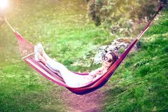 Outdoors relaxing leisure. Woman relaxing in hammock outdoors in a park Royalty Free Stock Photo
