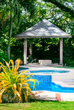 Outdoors relaxing swimming pool with gazebo and tropical garden Royalty Free Stock Images