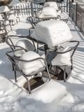Outdoors restaurant chairs and tables covered with thick snow cover. Empty chairs and tables covered with heavy snow cover outside restaurant Royalty Free Stock Photos