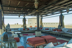 Outdoors restaurant comfortable lounge with tables and pillows on the top of the roof at luxury arabian desert resort Stock Photos
