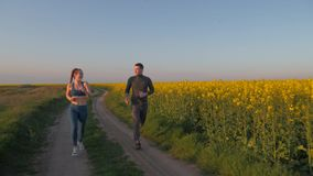 Outdoors running, happy sportsman and sportswoman with kanekalon braids run around on nature on flowers rape field. Against blue clear sky stock video footage