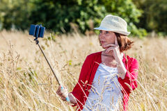 Outdoors selfie for beautiful 50s woman in high dry grass Stock Images
