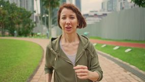 Outdoors slow motion gimbal shot tracking in slow motion young attractive and fit woman in hoodie running at green city park. In morning jogging healthy workout stock video footage