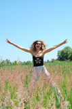 Outdoors summer happiness. Adorable young woman jumping in the floral field Stock Photos