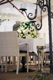 Outdoors table setting. An elegant outdoors table setting with chairs at a luxury hotel in Capri surrounded by flowers, partially behind an iron candelabrum and Royalty Free Stock Photography