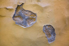 Outdoors wall texture with peeling yellow plaster. Background. Royalty Free Stock Images
