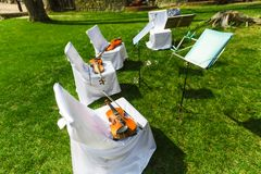 Outdoors wedding ceremony - string quartet's chairs with instrum Stock Image