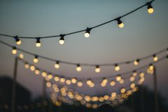 Outdoors wedding decoration with light bulbs at sunset Royalty Free Stock Image