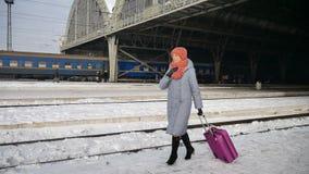 Outdoors wideo młoda kobieta w błękitnym żakiecie śpieszy w górę stacji kolejowej przy podczas zimy z purpurową bagaż walizką zbiory wideo