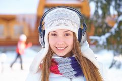 Outdoors on a winter day. Girl listen music. Royalty Free Stock Photo