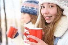 Outdoors on a winter day. Girls drink tea. Stock Images