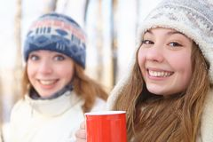 Outdoors on a winter day. Girls drink tea. Royalty Free Stock Photos
