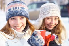 Outdoors on a winter day. Girls drink tea. Royalty Free Stock Image
