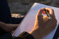 Outdoors writing session. Someone writing in a notebook royalty free stock photos