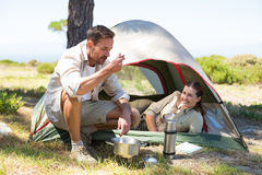Outdoorsy couple cooking on camping stove outside tent Stock Photos