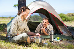 Outdoorsy couple cooking on camping stove outside tent Royalty Free Stock Image