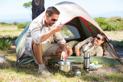 Outdoorsy couple cooking on camping stove outside tent Royalty Free Stock Photos