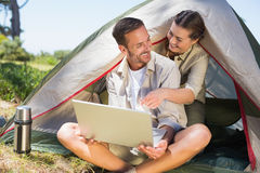 Outdoorsy couple looking at the laptop outside tent Royalty Free Stock Photography
