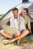 Outdoorsy couple looking at the laptop outside tent Stock Photography