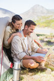 Outdoorsy couple looking at the laptop outside tent Royalty Free Stock Images