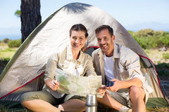 Outdoorsy couple looking at the map outside tent Royalty Free Stock Photo