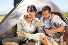 Outdoorsy couple looking at the map outside tent Stock Image