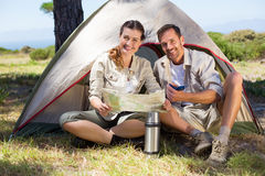 Outdoorsy couple looking at the map outside tent Royalty Free Stock Image