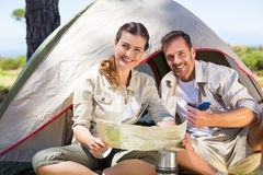 Outdoorsy couple looking at the map outside tent Stock Images