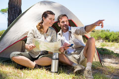 Outdoorsy couple looking at the map and pointing outside tent Royalty Free Stock Photos