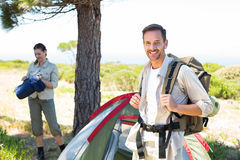 Outdoorsy couple setting up camp in the countryside Stock Photo