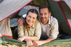 Outdoorsy couple smiling at camera from inside their tent Stock Images