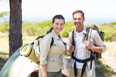 Outdoorsy couple smiling at camera outside their tent Stock Photo